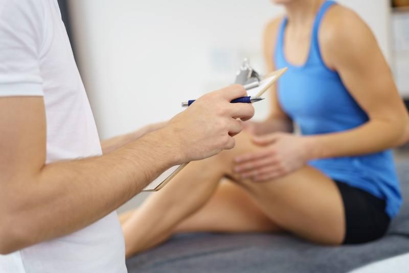 Eine Patienten bekommt Anweisungen für die Krankengymnastik vom Physiotherapeut