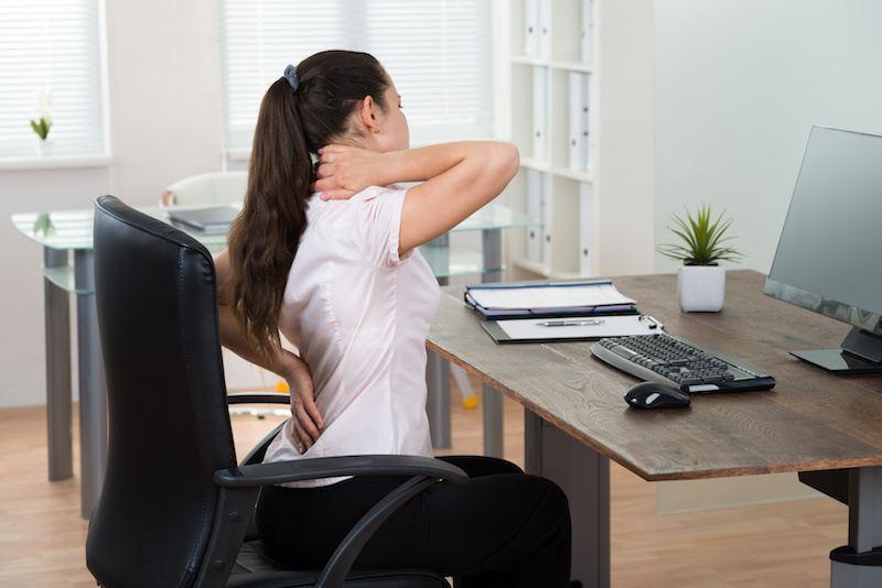 Eine Patienten klagt über Rückenschmerzen am Arbeitsplatz