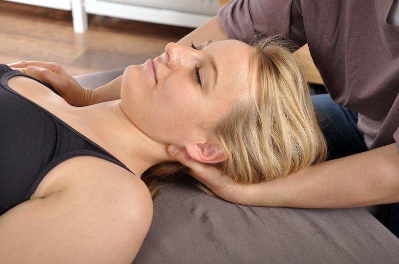 Eine Patienten erhält manuelle Therapie am Nacken