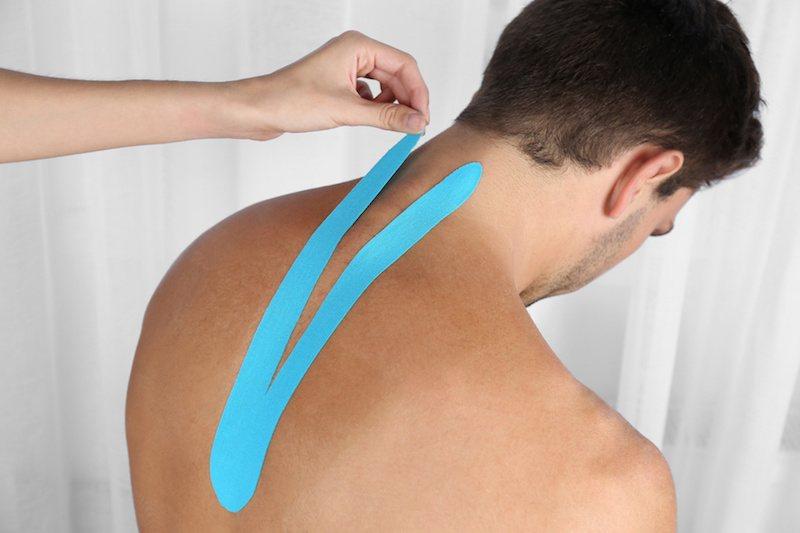 Ein Patient bekommt Kinesio Tapes an den Rücken